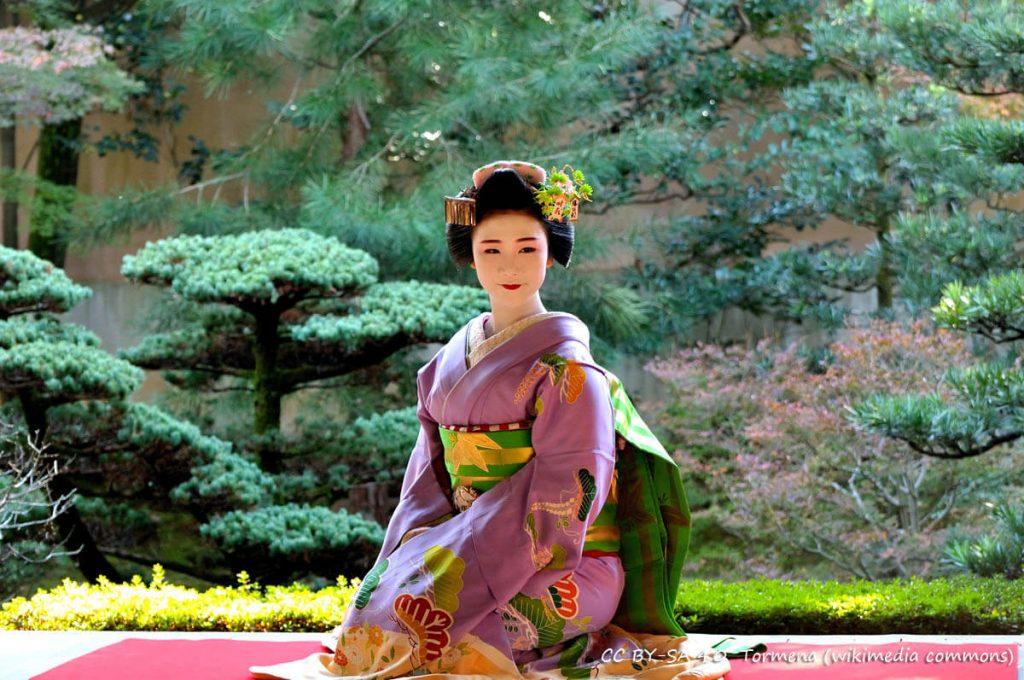 Maiko accovacciata prima di uno spettacolo